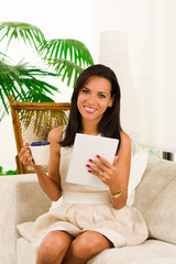 Beautiful young elegant woman sitting in sofa using tablet and