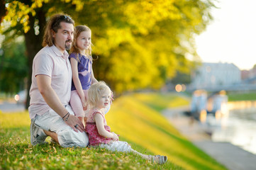 Young father and his daughters sitting by a river