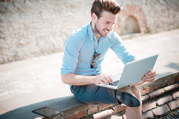 young handsome hipster modern man outdoor using notebook