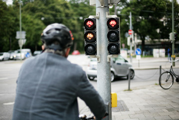 Mann mit Fahrrad vor der Ampel