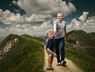 Son with father running on the footpath during highmountain walk