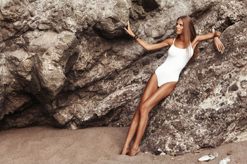 The young beautiful woman with tan on the beach, near the rocks