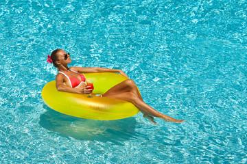 Sexy woman in bikini enjoying summer sun and tanning in pool