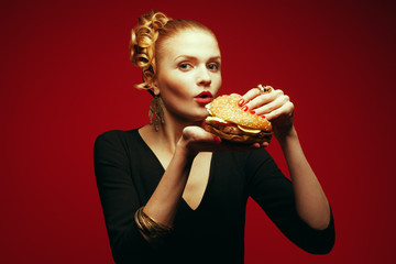 Fashion & Gluttony Concept. Model eating cheeseburger