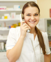 Portrait of a smiling female pharmacist on the phone