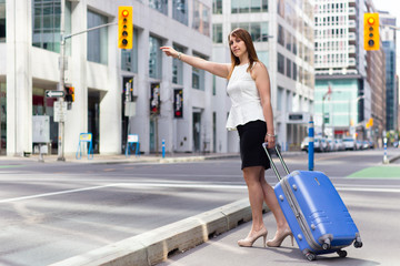 Traveling Business Woman Hails a Taxi on a city street