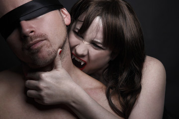 Female vampire bites man in the neck