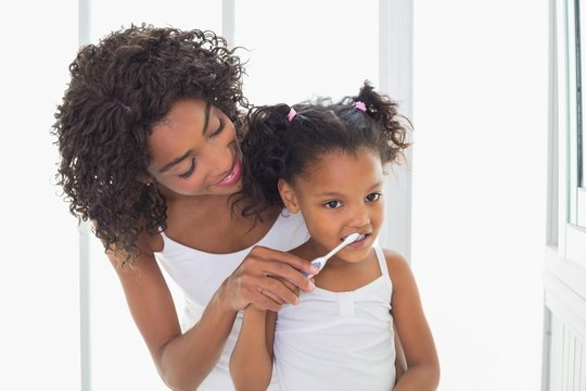Pretty mother helping her daughter brush her teeth