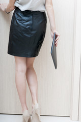 Rear view of a woman's body in a short  leather skirt.