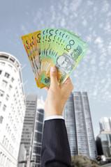 Hand holding money - Australian dollars (AUD)