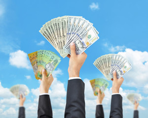 Hands holding money in multi currencies -money raising & funding