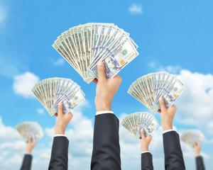 Hands raising money - United States dollar (USD) banknotes