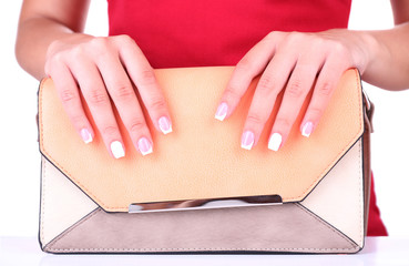 Female hand with stylish colorful nails holding colorful bag
