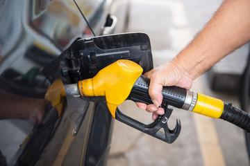 transportation concept - man pumping fuel in car at petrol stati