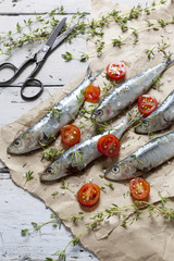fresh sardines with tomatoes slices and thyme on brown paper