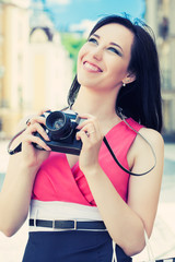 beautiful young woman taking photos with vintage camera on a cit