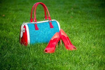 Fotobehang Picknick Shoes and women's handbag lay on the grass, women's shoes