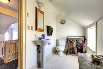 Simple light tone bathroom with vaulted ceiling