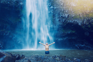 Wall Mural - Man in pool at the base of large waterfall