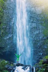 Wall Mural - Man standing at base of massive waterfall