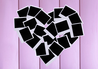 Photo papers in shape of heart on wooden background