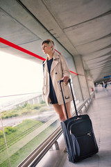 Businesswoman portrait with trolley at Charles de Gaulle airport