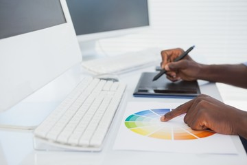 Designer sitting at his desk working with digitizer