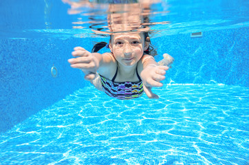 Happy underwater child swims in pool, girl swimming