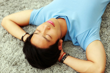 Young asian man sleeping on the carpet at home