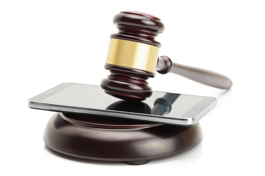 Smartphone under judge gavel isolated on white background