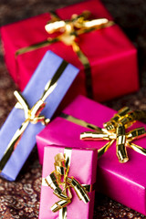 Four Wrapped Gifts with Golden Bows.