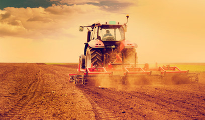 Wall Mural - Farmer in tractor preparing land for sowing