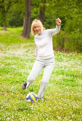 Mature woman kicking a ball