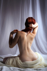 Back view of a naked woman sitting in bed
