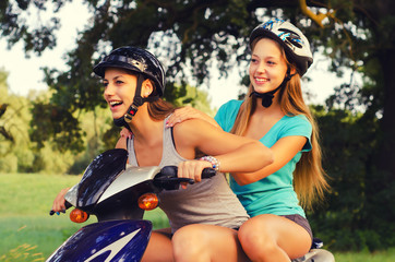 Two happy teenage girlfriends riding scooter