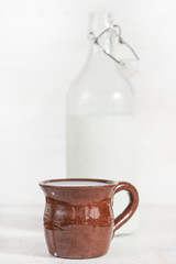 Fresh milk in ceramic mug and open old fashioned bottle