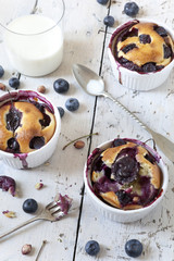clafoutis with blueberries and cherries with milk in glass