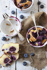 two clafoutis with blueberries and cherries on rustic background