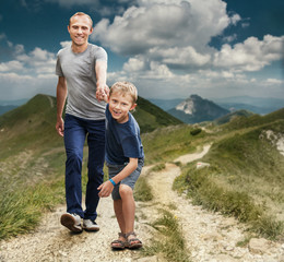 Son with father walking on the highmountain footpath