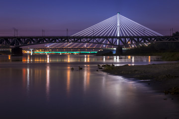Backlit bridge at night and reflected in the water