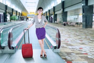 Businesswoman standing on escalator
