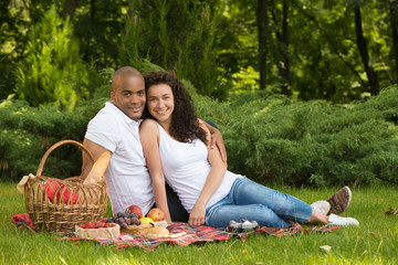Happy young couple enjoying picnic in a park