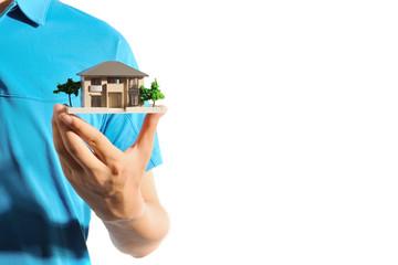 家の模型を手に持っている青いポロシャツのさわやかな男性