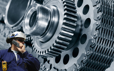 Wall Mural - engineer, worker with a giant gears and cogwheel machinery