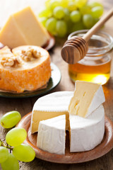 cheese plate with camembert, cheddar, grapes and honey