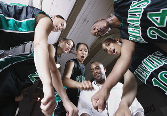 Girls basketball team in huddle with coach