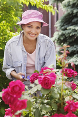 Portrait of woman pruning roses