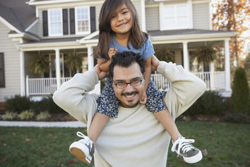 Portrait of father and daughter in front of house