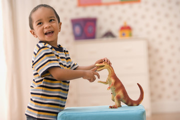 Young boy playing with toy dinosaur