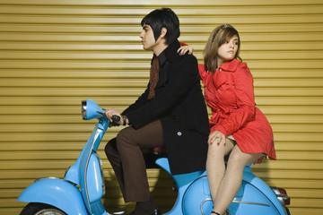 Young couple sitting on scooter